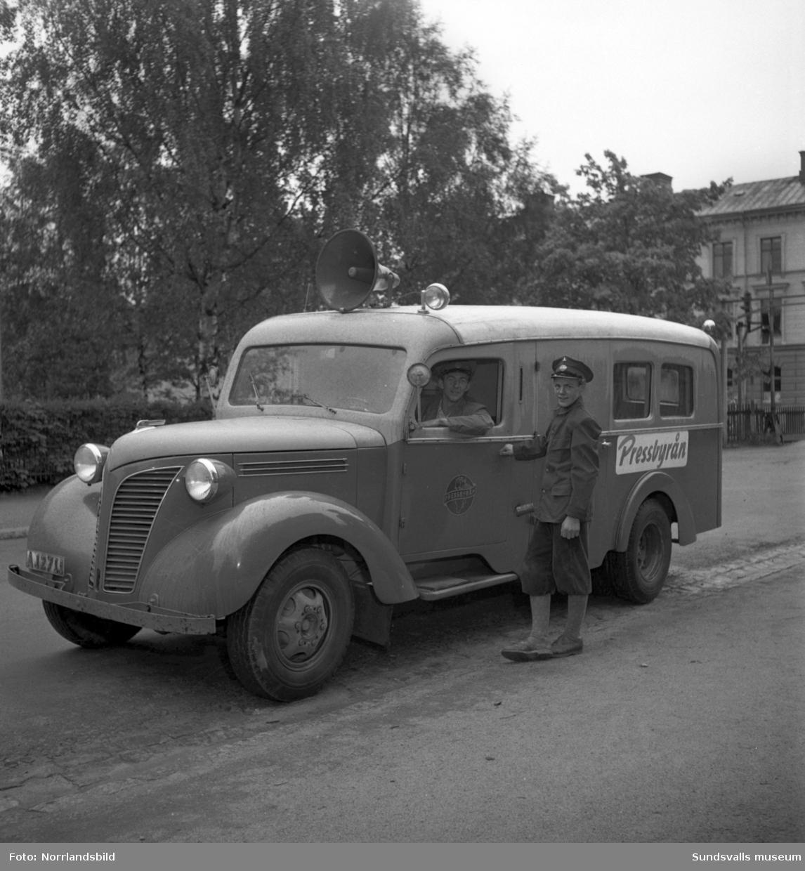 Pressbyråns distributionsbuss har stannat på Thulegatan vid järnvägen. Två män köper tidningar.