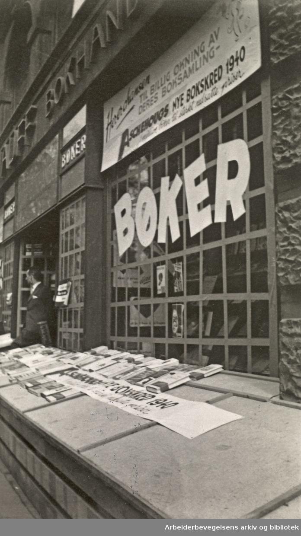 Ole M. Engelsens fotografier fra okkupasjonsårene i Oslo..Utstilling i Nils S. Hauff bokhandel i Karl Johans gate 45. Vindusrutene ble sikret for å hindre at glasset skulle splintres ved flyangrep. Lemmene og sanden skulle gjøre tilfluktsrommene i kjelleren tryggere.