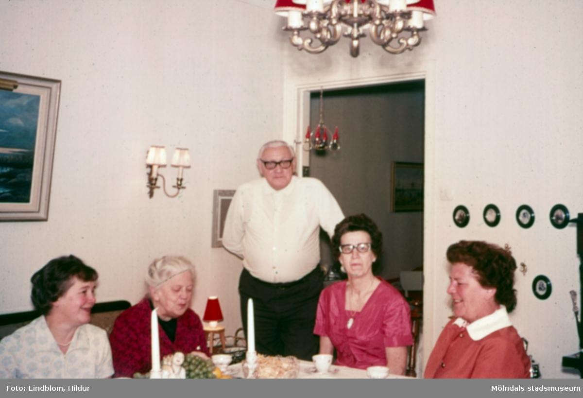 Fyra kvinnor och en man i ett vardagsrum, 1960-1970-tal. Fotografiet är möjligen taget hemma hos tant Hildur, d.v.s. Hildur Lindblom, som var delägare i Rasmussons skoaffär. Från vänster: Märta Sjöberg, tant Karin, d.v.s. Karin Gren, ägare av skoaffären, okänd man, Lisa Larsson, okänd kvinna.  För mer information om bilden se under tilläggsinformation.