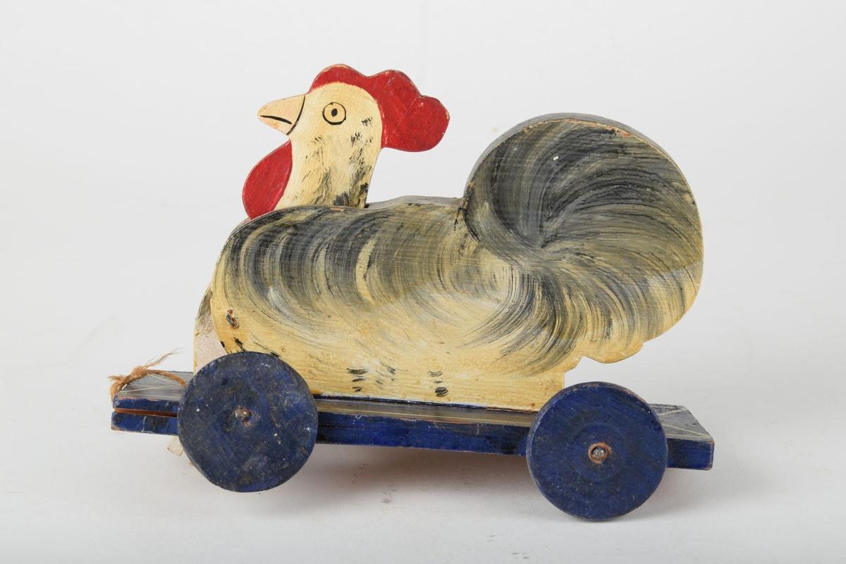 Hønefigur av tre festet på en treplate med hjul.  Det har trolig vært en draleke med tråd. Når man triller på leken beveger hodet til høna seg.