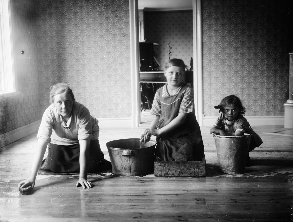 Sannolikt Helga och Helmy Melberg som skurar golv tillsammans med sin mor Frida Melberg, Revelsta gård, Altuna socken, Uppland 1918