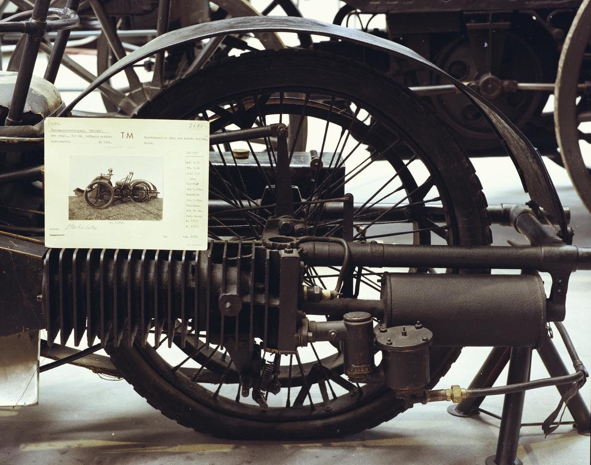 Bil med tre hjul, lågt byggd och av lätt konstruktion, inspirerad av samtida cykel- och mc-tillverkning med rörram och trådekerhjul. En eller två passagerare kan sitta framför föraren. Motorn startas i svänghjulet med vev och kraftöverföring från motorn till bakhjulet sker med flatrem. Med spaken på vänster sida sker växling genom att handtaget vrids. Drivning sker genom att spaken förs framåt och då spänns drivremmen. Vid bromsning förs bakhjulet framåt med spaken mot en fast bromskloss av trä som bromsar mot remskivan. En fotbroms verkar på motorns svänghjul.  Cylinder diameter: 76 mm. Cylindervolym 640 cc Slaglängd: 145 mm. Effekt: 2 hkr. Encylindrig luftkyld liggande fyrtaktsmotor. Tre växlar, ingen backväxel. Tysk Maybach förgasare. Tändning i cylindertoppen med ett glödrör av platina som värmdes före start med blåslampa. Ombyggt till tändstift. Högsta fart 60 km/tim Tankvolym 9 l, vilket räcker till 12-15 mils körning.