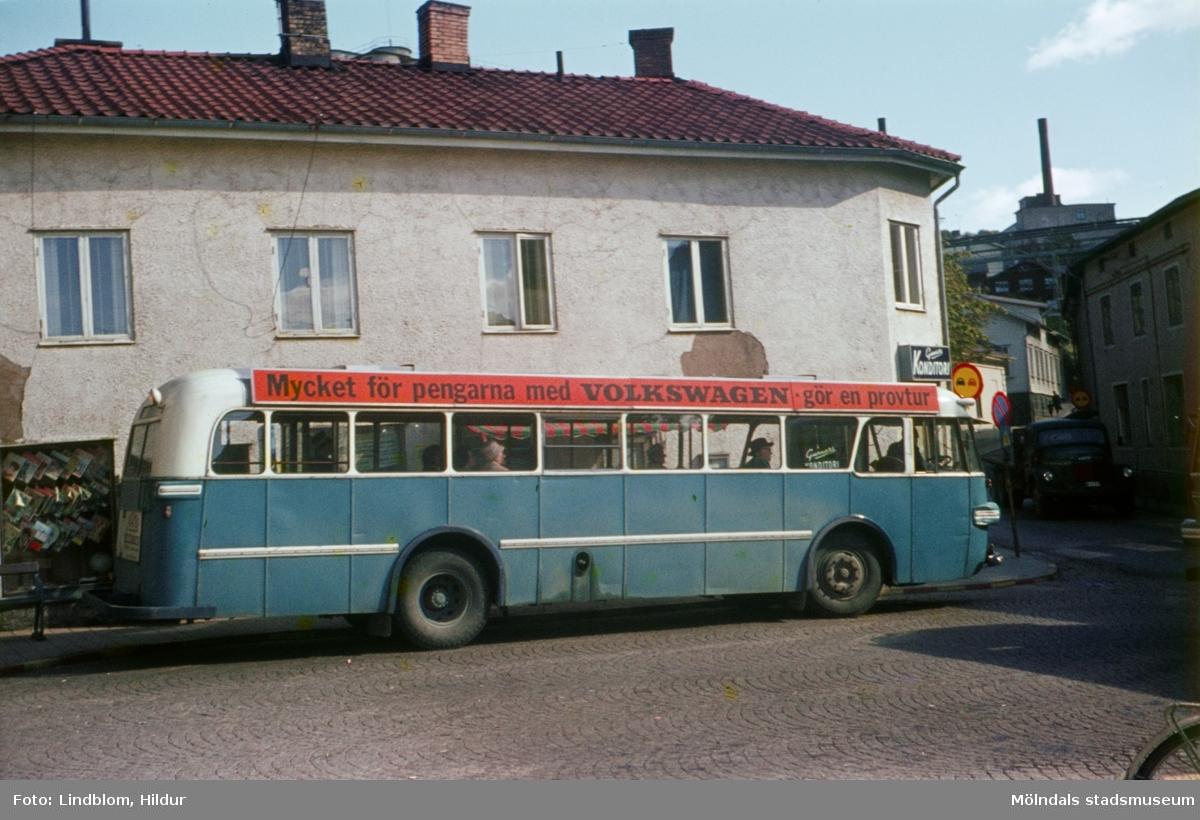 En blå buss framför huset Kvarnbygatan 45 vid Gamla Torget i Mölndal, 1960-tal. Till höger ses även del av Kvarnbygatan 6, byggnad tillhörande SOAB.  För mer information om bilden se under tilläggsinformation.