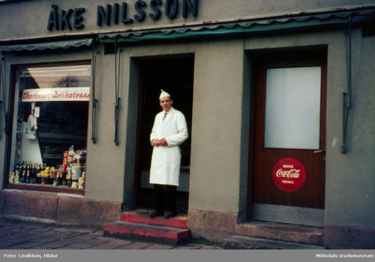 En man står i dörren till Åke Nilsson charkuteri och delikatesser med adress Kvarnbygatan 43 vid Gamla Torget i Mölndal, 1960-1970-tal.  För mer information om bilden se under tilläggsinformation.