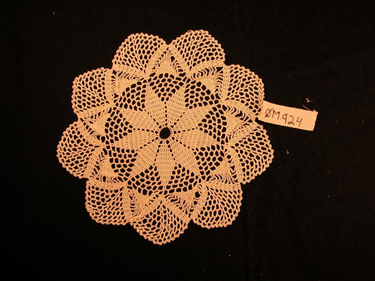 9 spisse blad rundt eit sirkelhol i sentrum, 9 meir runda blad ytst.