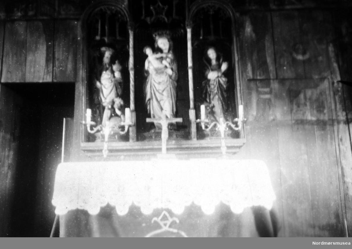 """På bildet ser vi altret i Grip Kirke, med den hvite alterduken, lysestaker og krusifiks. Øverste del av av den sengotiske altertavlen med gotisk fletteverk og renessanse rundbuer er utydelige. En ser disse figurene fra venstre til høyre, utført i tre: 1.) Sankt Olav med rikseple i venstre og øksen i høyre hånd, som tråkker på en syndens figur, en drageaktig skikkelse, med menneskehode dekket av en turban (arketypen """";tyrkeren"""";). 2) Jomfru Maria med barnet på armen. 3.) St. Margaretha (på Grip kalt """";Maret"""";) - en ung kvinne med to lange fletter i buer. Et hunde- eller ulvehode stikker frem foran føttene hennes. Til venstre ser vi inngangen til sakristiet, til høyre skimter vi litt av veggmaleriet """";Abrahams offer"""";, med Abraham kledt i renessansedrakt, med engler over, samt med litt av Isaak til høyre for ham. BIldet er datert august(?) 1947. Litteratur: Tone M Olstad: Alterskapet i Grip stavkirke, NIKU Rapport 5, 2003. Jostein Iversen: Grip, 1998. Fra Nordmøre Museums fotosamlinger."""