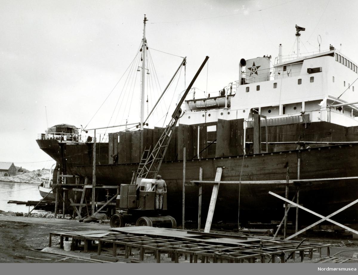 """Bildet er fra Storviks Mek. Verksted på Dahle ved Kristiansund. Bildet viser M/S""""Knoll"""" fra Ole T. Flakkes rederi på den nye patentslippvogna, den største slippen mellom Bergen og Trondheim, klinkbygget i stål 1918 og erstattet med nytt slippanlegg ca. 1979. Foran ses B/F""""Norddalsfjord"""" Storviks Mek. Verkstedets bnr.14 på beddingen og reisingen av dekkshuset. """"Norddalsfjord"""" ble levert til Møre og Romsdal Fylkesbåtar 15. mars 1961 og hadde følgende hoveddimensjoner: L 31,20 m x B 8,55 m x D 3,35 m og hadde en tonnasje på 159 bruttoregistertonn. Fremdriftsmaskineriet består av 3 Volvo Penta turboladede dieselmotorer type TMD96 på til sammen 420 hk som via kilremdrift var koblet til et felles gir og propellaksel med vribar propell, slik at hver enkelt av motorene kunne kjøres separat. Fergen hadde 2 Bolinders vekselstrømsaggregater type 1052MG på 23 hk hver tilkoblet en generator på 17 kW. Fergen var utstyrt med elektrohydraulisk styremaskin. Fergen har plass til 18 personbiler og har sertifikat for 160 passasjerer. Forut er det innredet 6 lugarer for offiserer og restaurantpersonale og akterut en mannskapslugar for 4 personer og toppfarten er 11,4 knop og marsjfarten 10,5 knop. Ferga er verkstedets første nybygg etter B/F""""Trygge"""" som ble levert i 1938. I forgrunnen ses verkstedets mobilkran av fabrikat Jones KL22, og med forlenget egenlaget bom, som holder en stålplate på plass og ble anskaffet ca. 1959. På bakken ses sveiseplanet. Personen i mobilkrana er sjauer Gunnar Pedersen. Bak M/S""""Knoll"""" ses en båt som slipsettes på såpehellingen fra 1901 og bak ses også Høttneset   (tidligere kalt Aakvikbergene) og Høttnesbrygga. Bildet er fra 1960. (Info: Peter Storvik) -- """"19/9."""" Foto fra anleggsområdet til Storvik Mekaniske Verksted på Dale, Nordlandet i Kristiansund, hvor vi ser fra et fartøy ved kaien, med en mobil heisekran like ved. Bildet er datert 19.09.1960. Fra Nordmøre Museums fotosamlinger."""