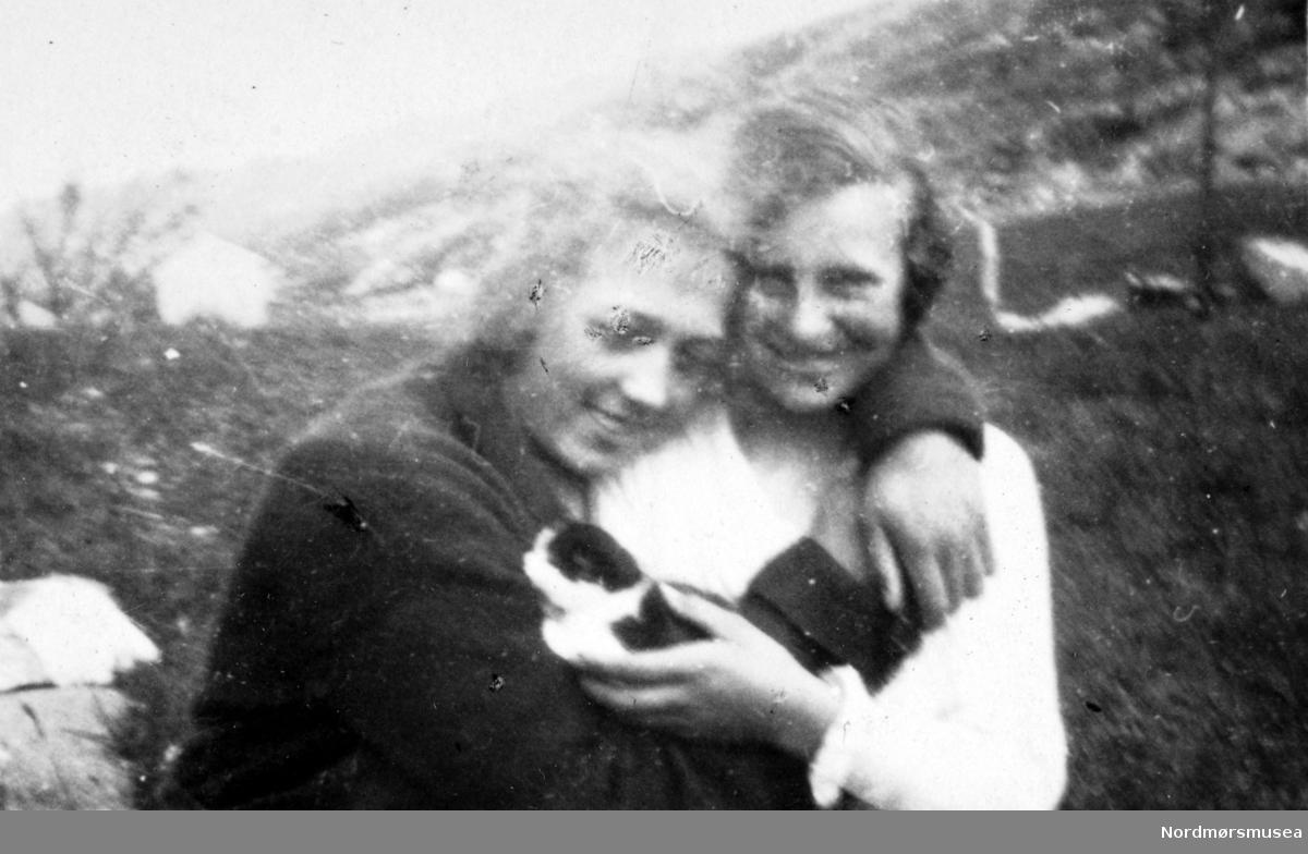To kvinner med en kattunge. Bildet ble gitt til Nordmøre museum av Nelly Rødsand 5. september 1983. Fotoalbumet består av bilder med reg. nr. KMb-1983-024.0049 til KMb-1983-024.0223. Flere bilder fra andre album er å finne på samlingsnummer KMb-1983-024. Fra Nordmøre museums fotosamlinger. EFR2015