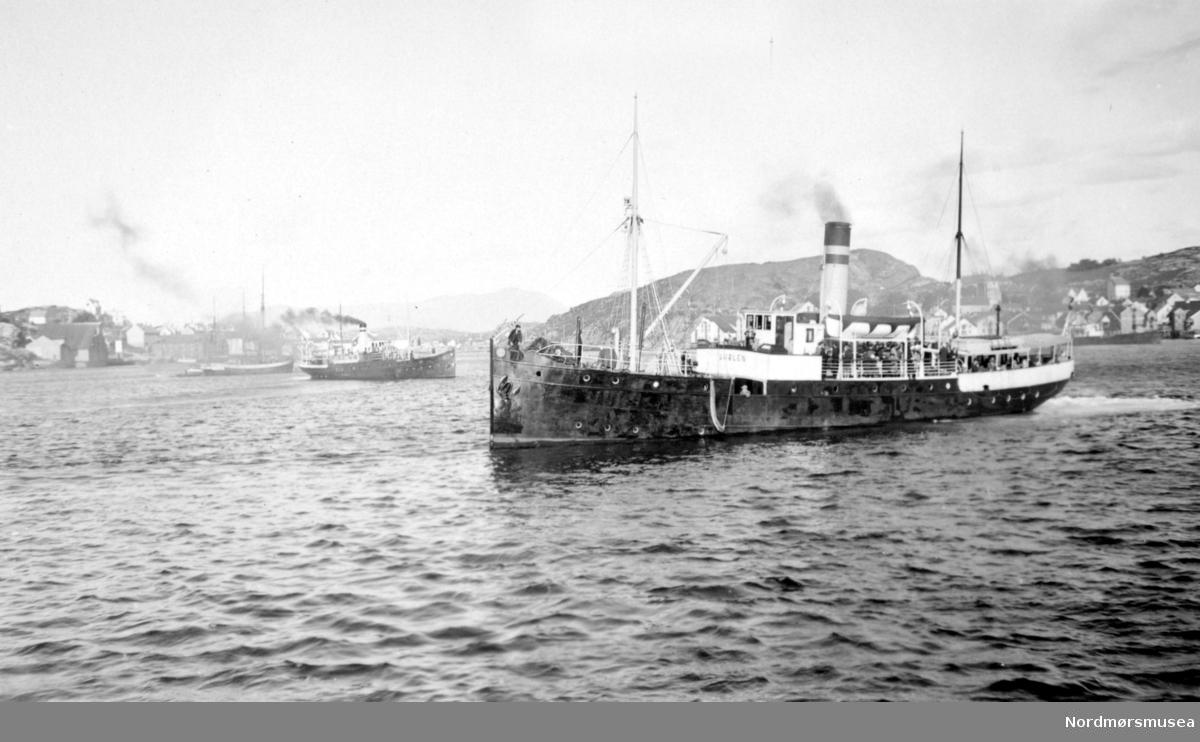 """Ute i havnebasenget ser vi flere av rutebåtene som gikk i trafikk til og fra kristiansund, med d/s Smølen i forgrunnen. Mange som kom og dro med disse båtene i helgene var ukependlere som dro hjem fra jobb på Lørdager, og tilbake igjen på Søndager. På grunn av dette ble båtene ofte kalt for """";pappabåter""""; på lokalmunne. Fra Nordmøre Museum sin fotosamling."""