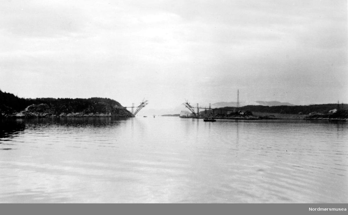 Omsund bru under konstruksjon. Omsund bru krysser Omsundet mellom øyene Frei og Nordlandet i Kristiansund kommune. Broen er 281 meter lang og ble tatt i bruk april 1940, men fikk ingen offisiell åpning på grunn av utbruddet av 2. verdenskrig. Broen ble prøvd bombet av tyskerne, men holdt, men 15 år gamle Ingolf Vatten som syklet over broen da tyskerne bombet broen ble drept. Broen var også viktig da Kristiansund ble evakuert. Broen ble liksom åpnet offisielt 24. april 2005, 65 år etter at den ble tatt i bruk. Per i dag 2008 er denne broen bare åpen for fotgjengere og en ny bro ved siden av den gamle er blitt bygd. Denne er en del av riksvei 70. Fotograf er usikk, men sannsynligvis Georg Sverdrup. Fra Nordmøre Museums fotosamlinger. Kilde: http://no.wikipedia.org/wiki/Omsundbrua