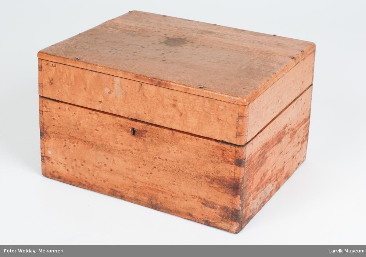 Teknikk: treplatene festet sammen ved plugging av endene i flettebitene. kantene på hjørnene forsterket med hjørnebeslag av messing, Form: oppdelt i 9 rom:8 åpne firkantede hvorav 4 har målene 5,1x6,2cm, 4 har målene 5,9-6,5x6,2cm,et av- langt rom med lokk har målene 5,7x23,7cm. hekte av jern(for å holde lokket oppe)montert på innsiden til venstre plate, malt med messingfarge. topp-plata festet i sideplatene med 16 jern- stifter og 3 messingskruer.