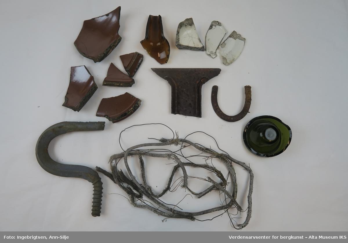Tingene, med unntak av hestesko og krok, er ødelagte/fragmentert. Det er fragmenter av keramikk og porselen, to glassbiter fra flasker, en ledning med metallstrenger, stor krok og en liten hestesko.