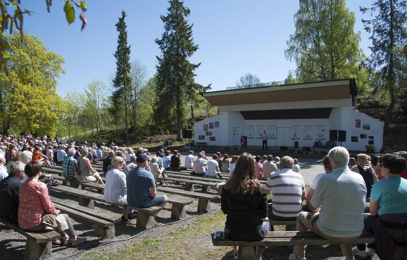 Friluftsscene med artister på og trebenker fylt med publikum (Foto/Photo)