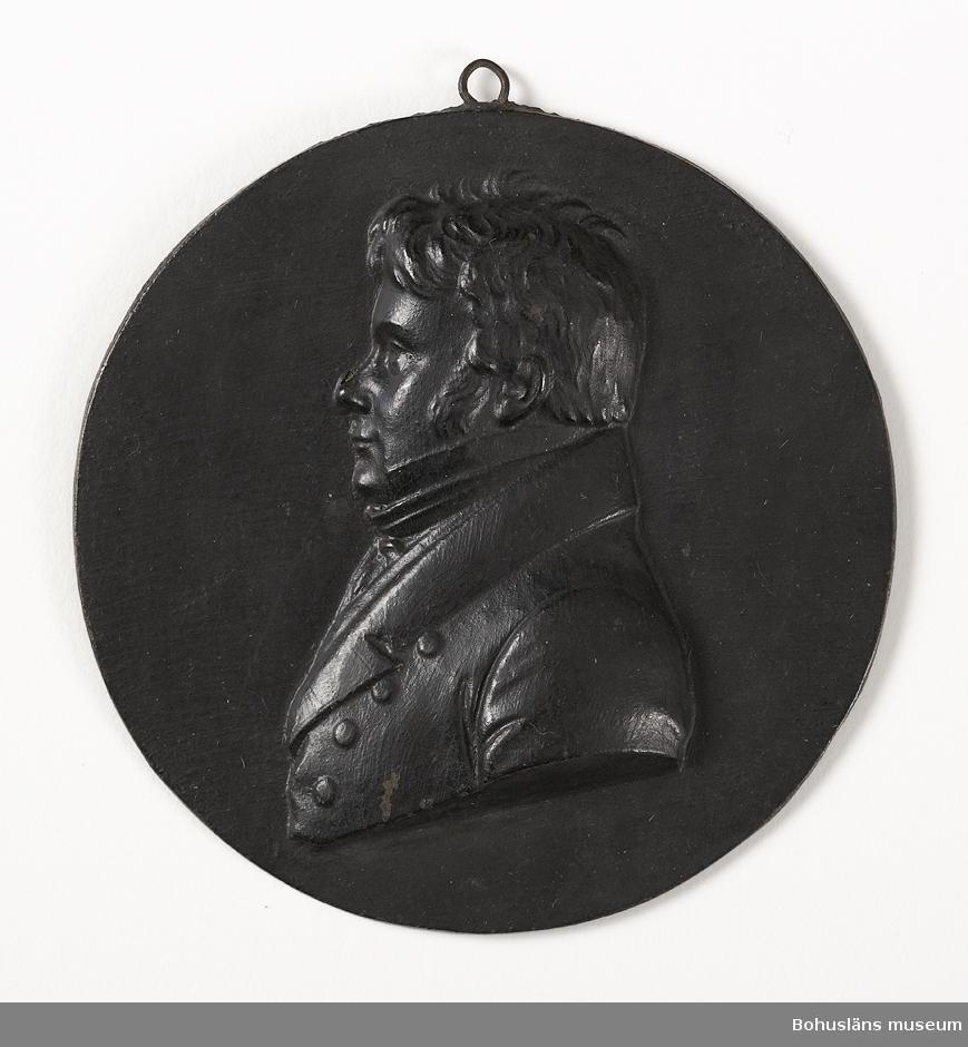 Ur handskrivna katalogen 1957-1958: Metallplåt med porträtt Diam: 8,7. Porträtt i profil i relief. Föremålet helt.