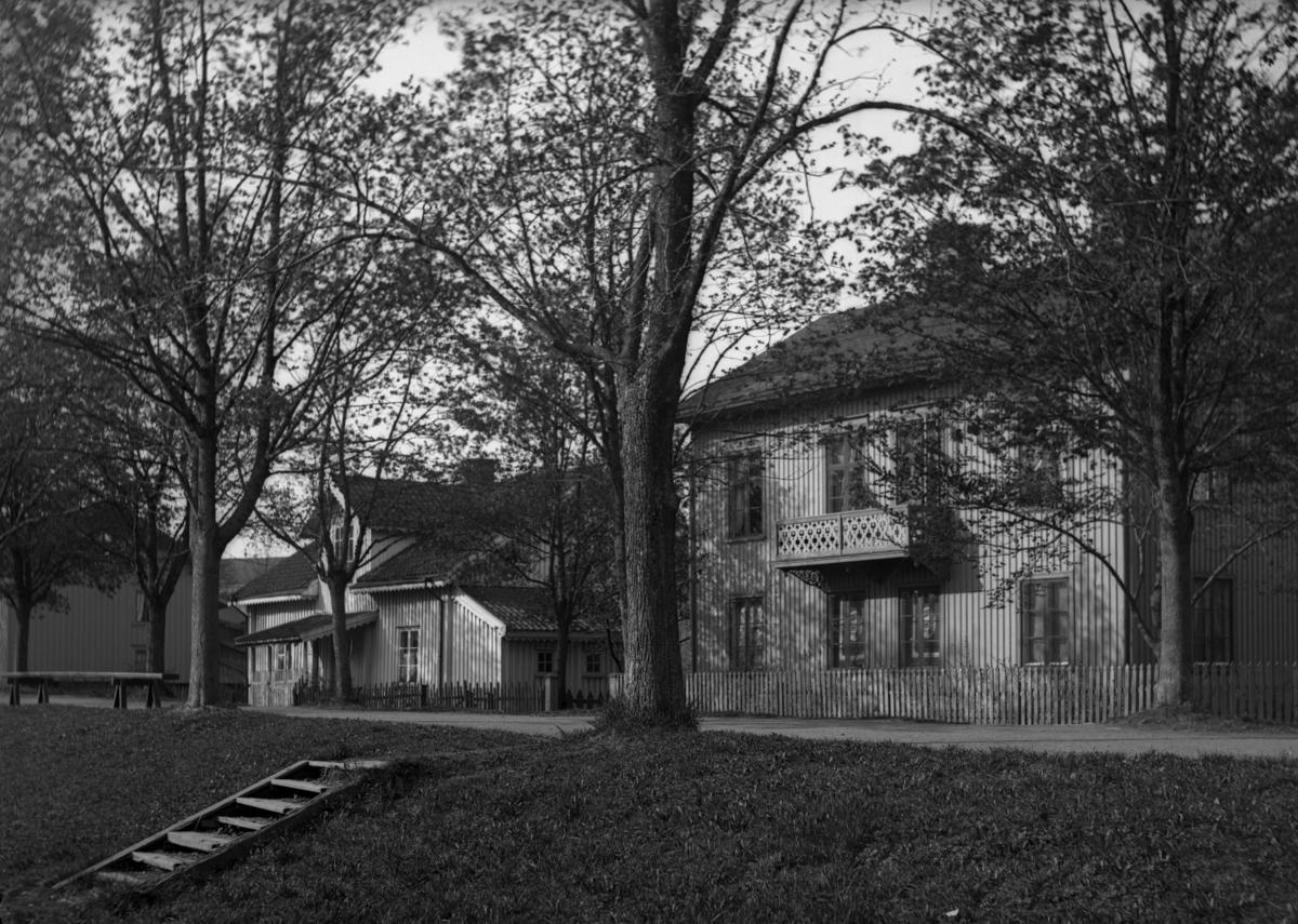 Trähus längs Västra Kanalgatan från hörnet med Herrgårdsgatan i kvarteret Gruvan. Det vänstra byggdes några år innan branden 1865. Bilden tagen runt 1900.