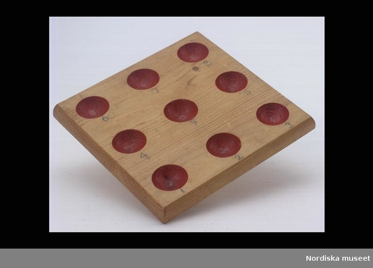 """Katalogkort: """"Spelbräda av trä, okänt spel. Av furu, fyrkantig form, fernissad, med 9 st. halvrunda hål, rödmålade, numrerade 1-9. 1900-t. början."""""""