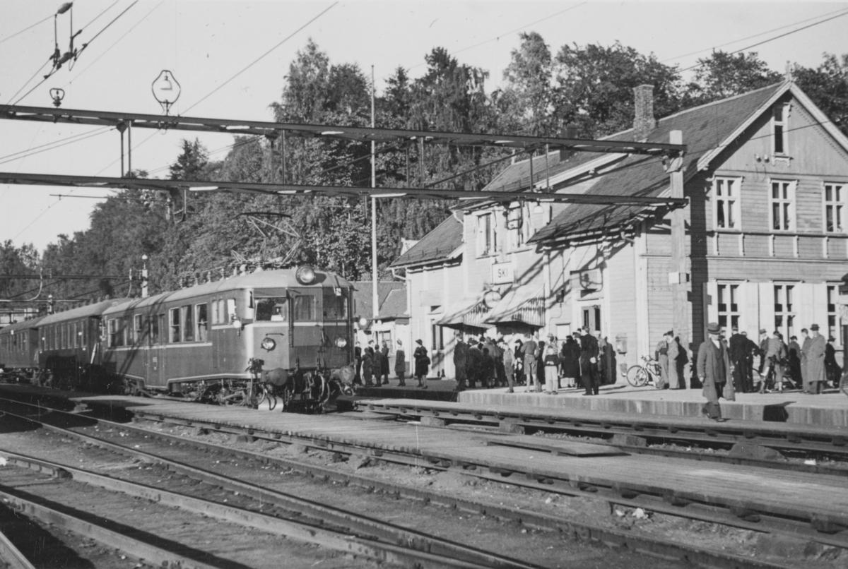 Ski stasjon ved åpningen av elektrisk drift Oslo Ø - Ski. Tog fra Oslo Ø bestående  av motorvogn type Cmeo 105a og to vogner kjører inn på stasjonen.