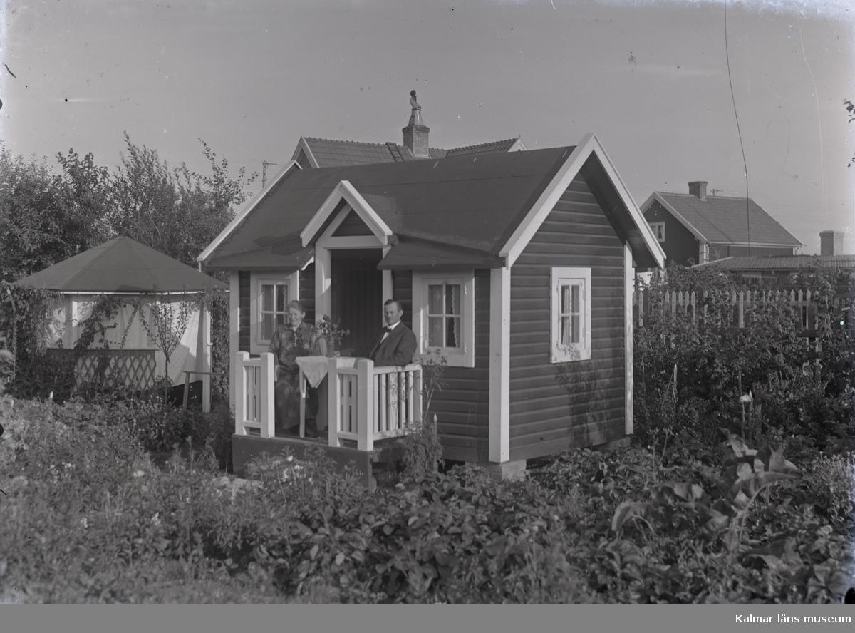 En stuga, man och kvinna i Kalmar södra koloniområde, fotograferat omkring 1930. Kalmar södra koloniförening grundades 1917 och har idag 105 kolonilotter. Området ligger strax söder om länssjukhuset i Kalmar med huvudingång från Stensbergsvägen.