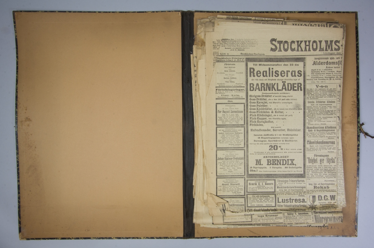 Portfölj av marmorerad papp. Sammanhållen med knytband. Rygg av svart linne. Innehåller enbart flera exemplar av Stockholms Tidningen från 1911.