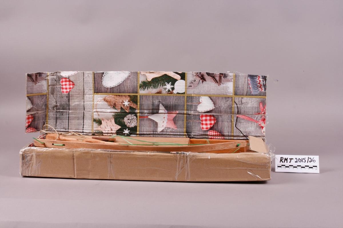 Pappkasse til instrument. Brun papp på utsiden, innersiden er trukket med julepapir med mønster. Kan åpnes med et lokk. Yttersiden er teipet med gjennomsiktig teip.