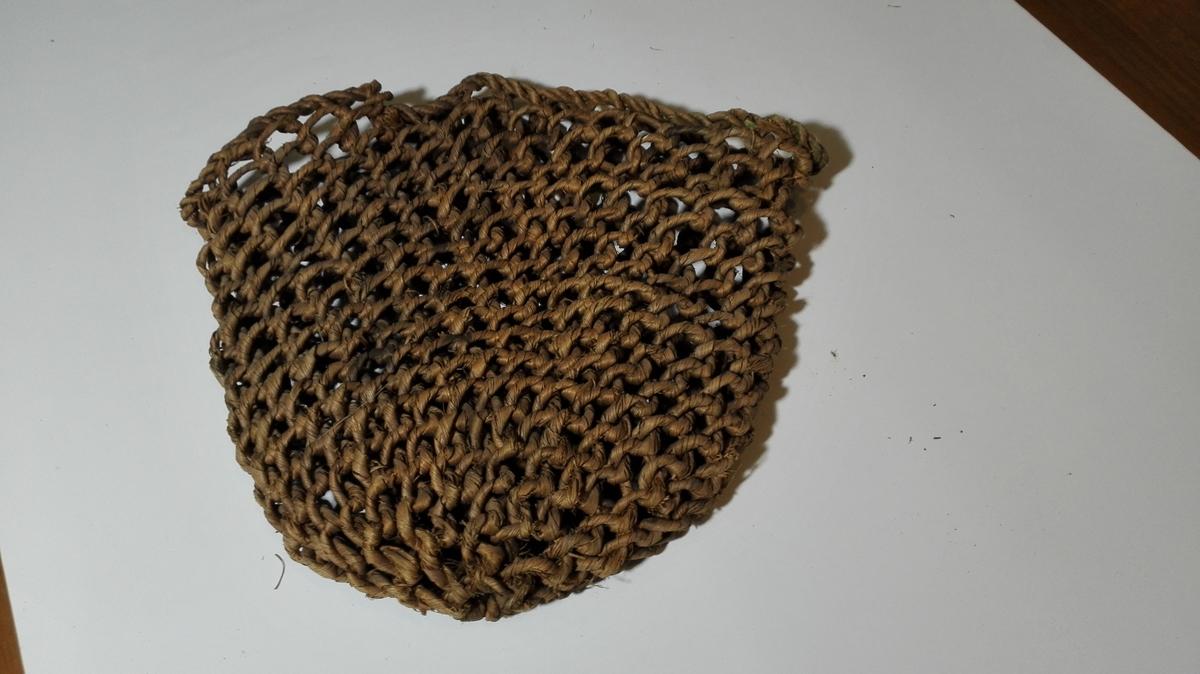 1 bastetaugpose.  En pose laget av spundet bastetaug.  Posen sammenlagt har en höide av 45 cm, bredde överst ca 50 cm og er nedentil avrundet. Posens oprindelige anvendelse ukjendt, da den er meget gammel. Har i senere tid været brukt tilat bære fersk fisk i.  Gave fra gaardbr. Per Tönder, Dyrdal, Næröen.