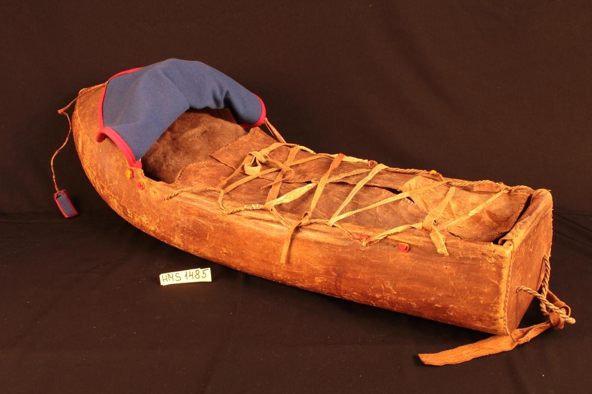 Komsen er lagd av en uthult trestamme som er båtformet og breiere øverst enn nederst. Denne er trukket med barket reinskinn og utstyrt med en kalesje i blått ullklede. Fra forkanten på kalesjen går det skinnsnorer ned til fotenden som tar av for støt under bæring og reiser. I ble barnet snørt omhyggelig ned i kluter og fine skinn av reinkalv, hare eller lam. Spedbarnet hviler på et underlag av hvitmose eller lange, myke reinhår samt på tørket knusk frabjørk. Barnet kan derfor også være ute i sterk kulde. En komse med barn kan fraktes i pulk eller kløv, henges opp på en grein eller stilles på ende ned i snøen mens mora gjør arbeidet sitt.  Ytterligere Opplysninger på kartotekkort.