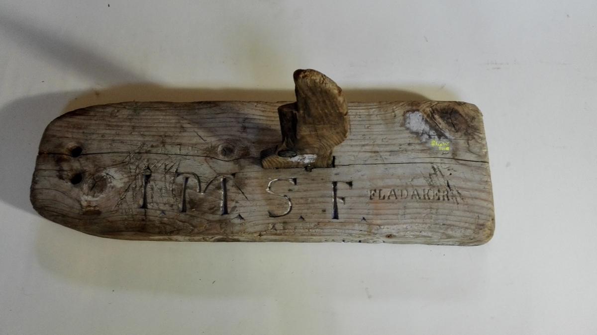 """Form: Rektangulær fjæl/klosse m/2 hol for tau i framenden. Nedfelt oppståande sentrert profilert fjæl som markering. Kvar eigar hadde sin profil og initialer på vakefjæla. Fjæla """"vakte"""", flaut på vatnet/sjøen og markerte kvar garnet, lina var sett."""