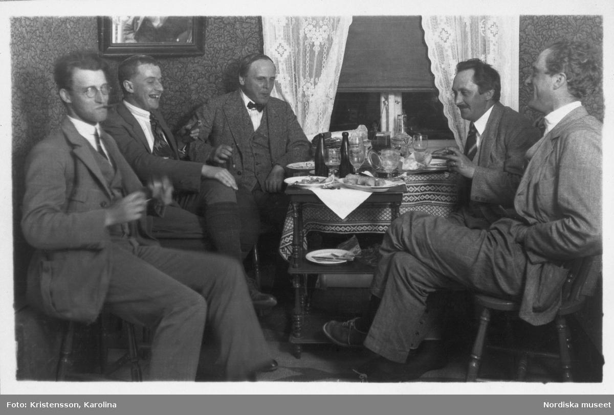 Fem män sitter runt ett bord på Älvdalens gästgivaregård och äter en måltid. från vänster fotograf Olle Ekberg, fil. dr. Bertel Hintze, intendent Sigurd Erixon (expeditionens ledare), antikvarien Ola Bannbers och arkitekt Mogens Mogensen. Bilden är tagen under Sigurd Erixons expedition i Ovansiljan 1926.