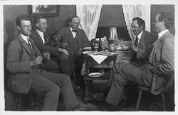 Fem män sitter runt ett bord på Älvdalens gästgivaregård och