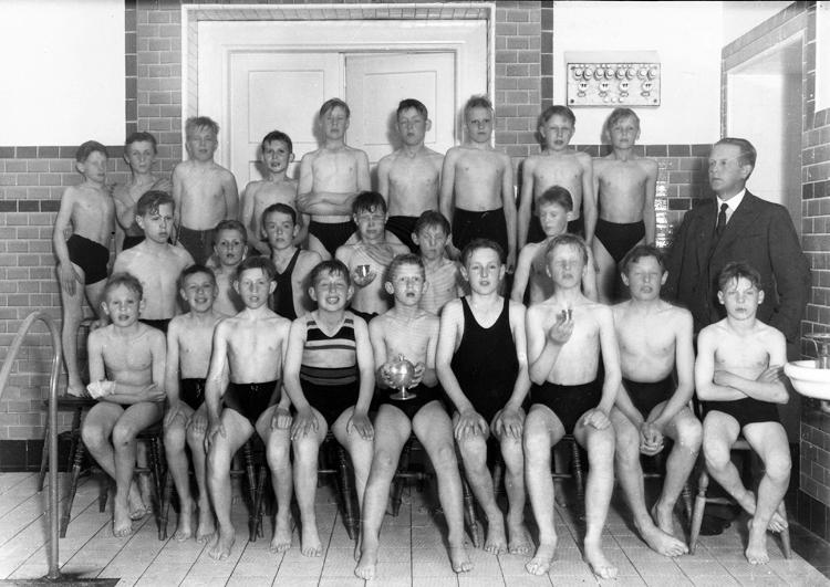Foto av ett gäng pojkar, klädda i badbyxor. De har samlats i ett hörn av simhallen tillsammans med sin ledare.