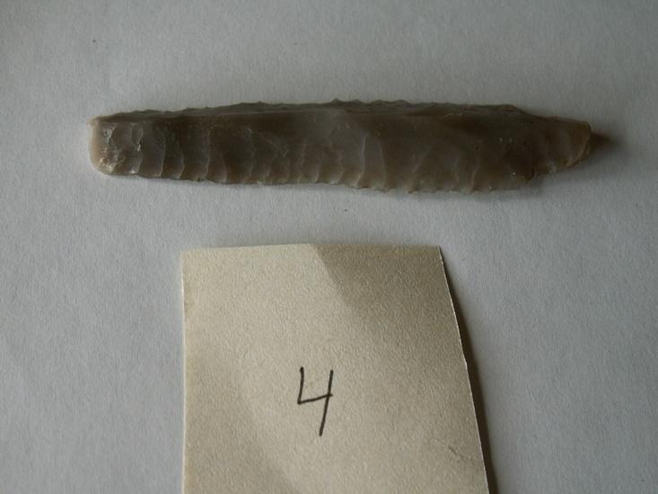Tångepilspets Foto av 3-sidig tångepilspets av flinta. Uppges vara hittad vid grävning för flaggstång av en Tage Andersson. Spetsen förvarades 2008-05-19 hos familjen Fürst på Oshults gård.Raä 217 a, 2008-04-09, reg i FMIS.