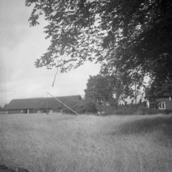 Foto av en äng med en brunn.I bakgrunden skymtar en lada oc