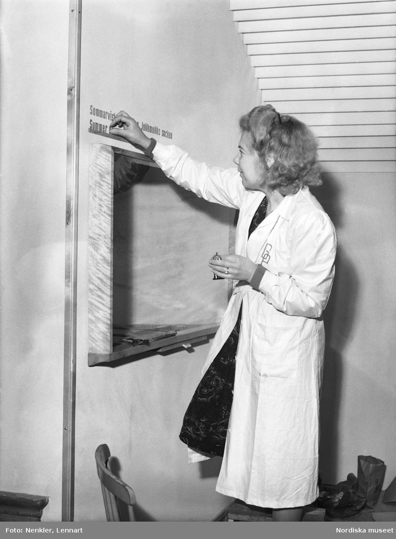 Textmontering i utställningsmiljö, fru Perny fäster bokstäver ovanför monter. Miljö från Lapska avdelningen på Nordiska museet. Skådesamlingens nymontering från 1947.