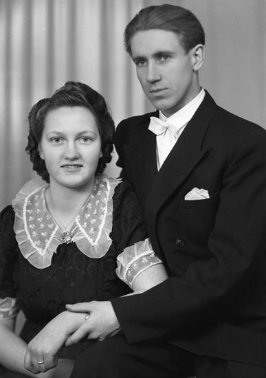 Foto av ett ungt par (bröllopsvittnen ?). Hon är klädd i mörk klänning med ljus ryschkrage m.m.. Han är klädd i frack (?) med vit fluga.Midjebild. Ateljéfoto.