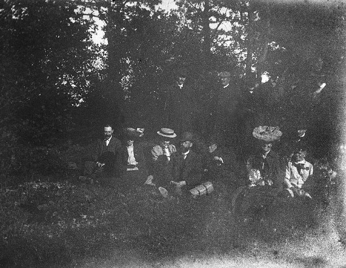 Foto av en grupp människor som slagit sig ner i en skogsglänta.