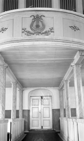 Foto i kyrkan mot dörren i gången.