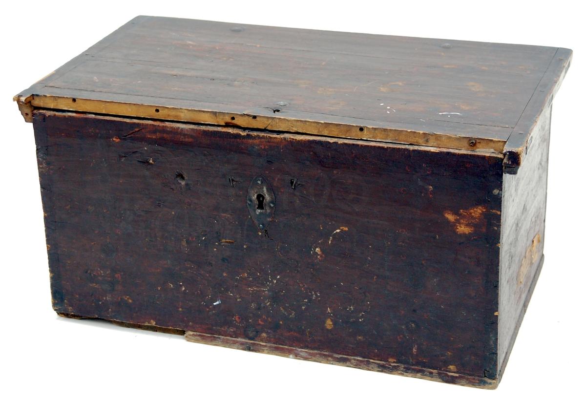 Kista, av furu, brunmålad, med platt lock och inuti läddika, till höger. Inuti vit med blommotiv i rött, gult, grönt, blått samt HID 1816.