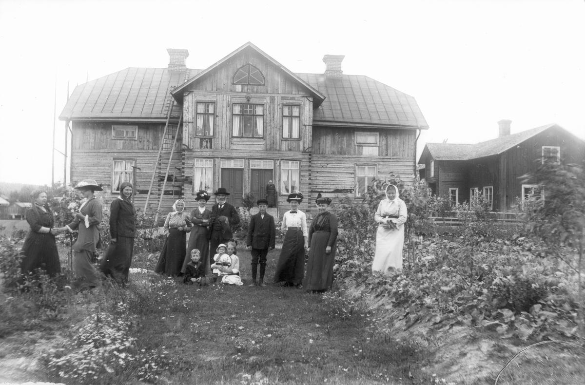 Skinnars, Lenninge 6:14. Byggnaden till höger bortriven på 40-talet. Tredje kvinnan från höger är Brita Persson, längst till höger Marta Hansson. I mitten med skärmmössa Evert Svedlund.