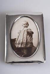 """Denne første gjenstanden er et innrammet fotografi av Kirsten Flagstad som ung pike. Allerede som 1-åring hadde musikaliteten begynt å vise seg og hun kalte seg selv for """"Titten Tangerin"""", eller Kirsten Sangerinne. Maja Flagstad og Michael Flagstad, hennes foreldre,  var anerkjente musikere i Kristiania. Bildet er tatt i 1896 og er en del av en serie med familiebilder. (Foto/Photo)"""