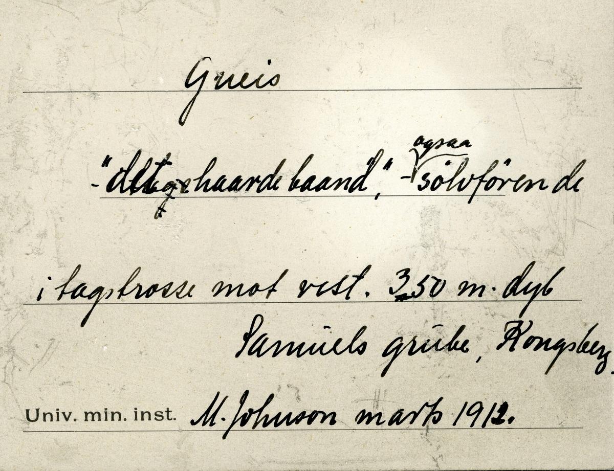 To prøver i eske Etikett i eske: Gneis «det haarde baand» - ogsaa sølvførende  i tagstrosse mot vest. 350 m. dyb Samuels grube, Kongsberg. M. Johnson marts 1912.  + papirlapp