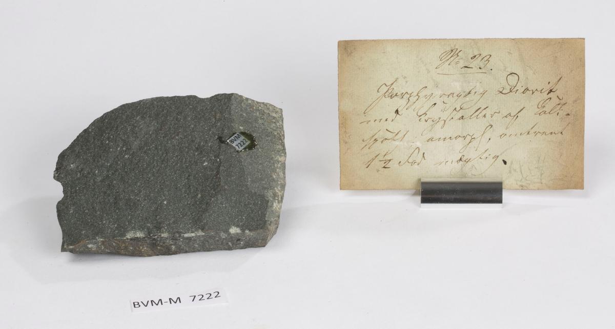 Etikett på prøve: 23.  Etikett i eske: No. 23. Porphyragtig Diorit med Krystaller af Kalk- spath, amorph, omtrent 1 ½ Fod mægtig.
