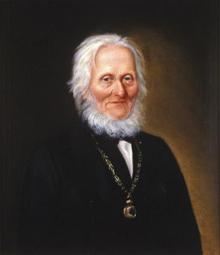 Portrett av Arnoldus v. W. S. Koren. Mørk drakt, medaljong (eller klokke?) i kjede rundt halsen