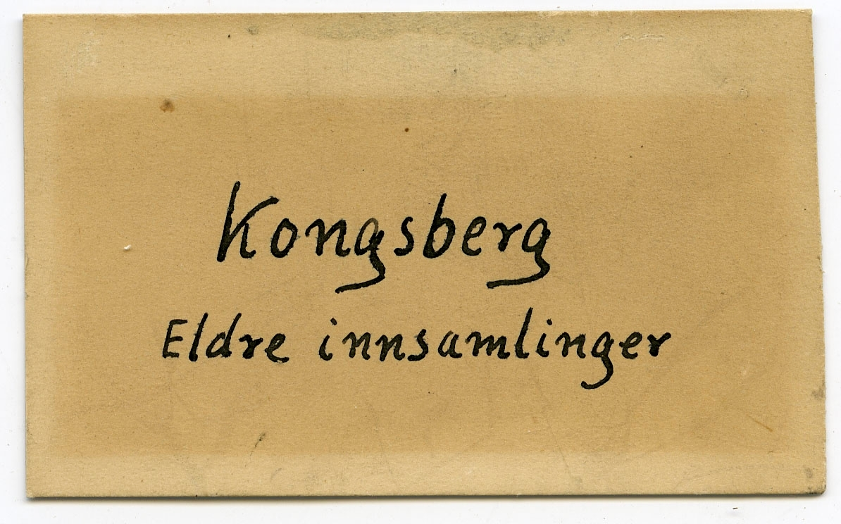 Etikett på prøve: 14.  To etiketter i eske: Etikett 1: No. 14 Chloritbildning skifrig, med megen Glimmer og lidet Kies.   Etikett 2: Kongsberg Eldre innsamlinger