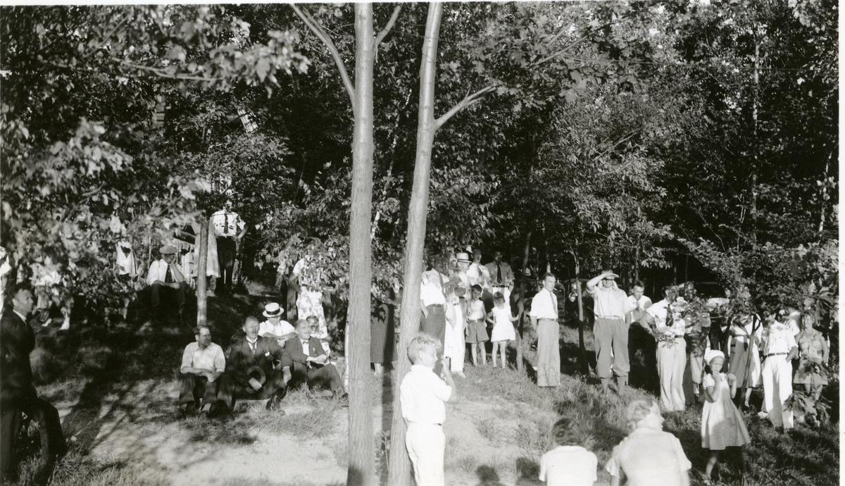 Olaus Islandsmoen sitter til venstre i bildet, med hatt i hånda. Han sitter i en park og det er mange kvinner, menn og barn der. Kan de være tilhørere på et stevne? Dette er i Amerika i 1934.