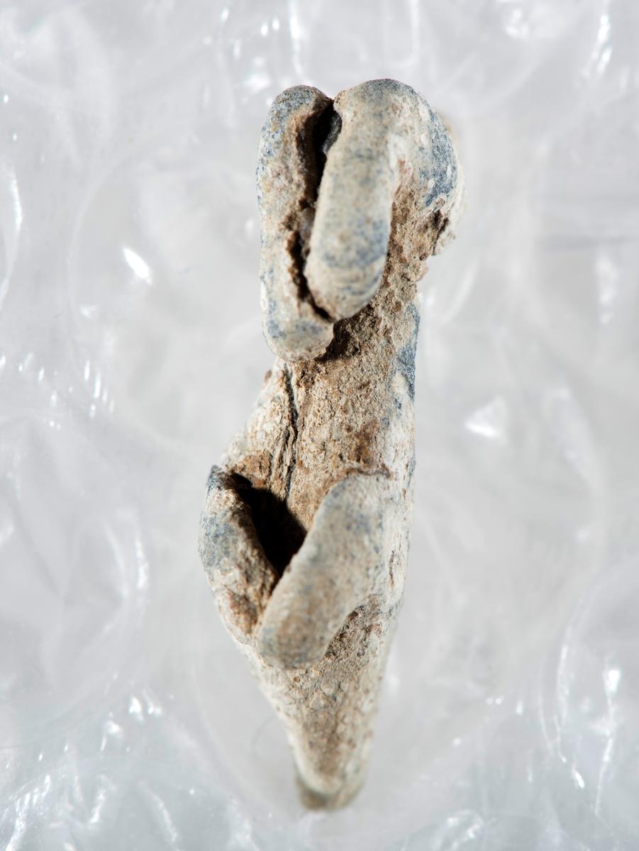 En svært nedslitt liten blygjenstand, avlang og deformet, men fortsatt med form som et lite dyr. Kroppen er avlang og med fire til dels sammenkrøllede og avbrekte bein. Dyret har også rester av en hals med punslede dekorelementer. hodet er faklt av.  Vi ser også en kort halestubb, den kan opprinnelig ha vært lengre. på ryggen er en fordypning og en annen større skade. Vi kan ikke avgjøre om gjenstanden er en hest eller en løve. Den er trolig for liten til å primært være et leketøy, men det kan tenkes at den har vært et vektlodd. Det er kjent av avansert utforming av vektlodd ble brukt for å forhindre forfalskning. Men noe sikkerhet om gjenstandens bruk har vi ikke.