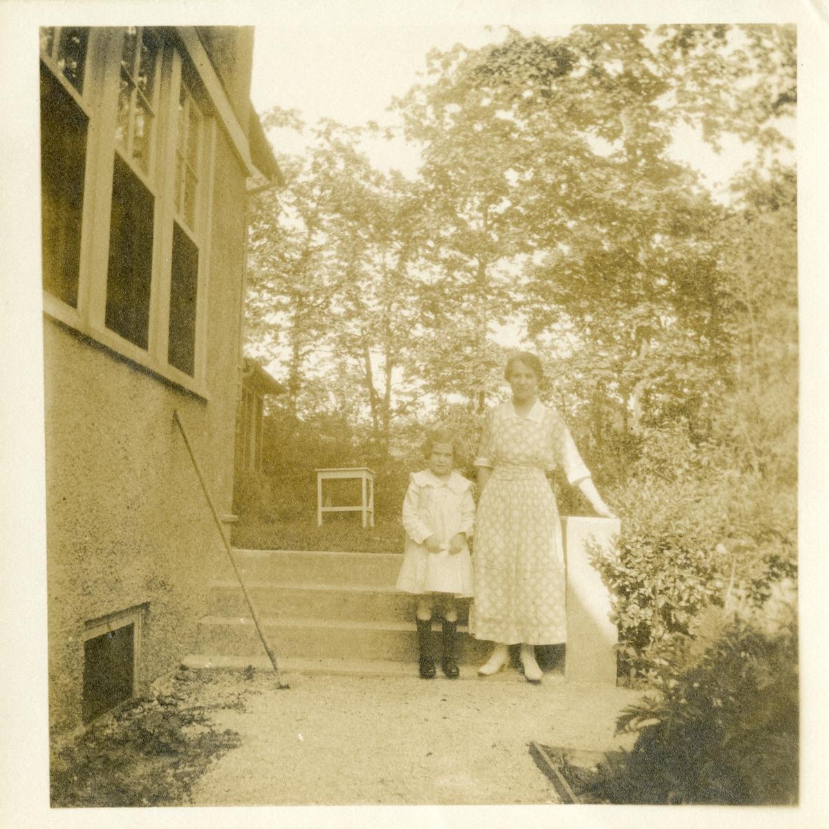 Kvinne og jente ved ei trapp utenfor et hus. Kvinna har lang blomstrete kjole, med hvit krage og hvite sko. Jenta har lys kjole med stor krage og mørke sko og knestrømper. Foto tatt i Amerika.