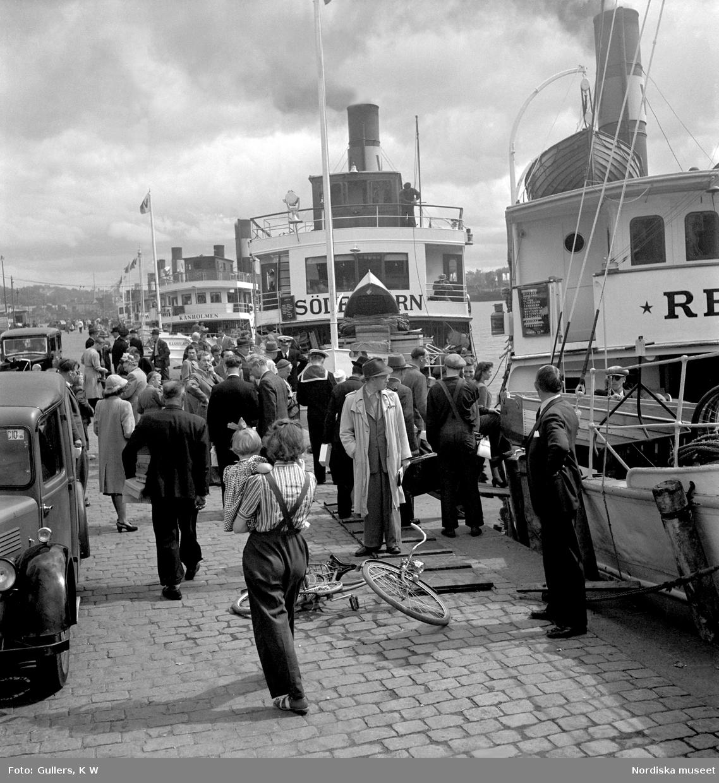 Nybroviken, Stockholm. Folksamling på Nybrokajen, skärgårdsbåtar i bakgrunden.