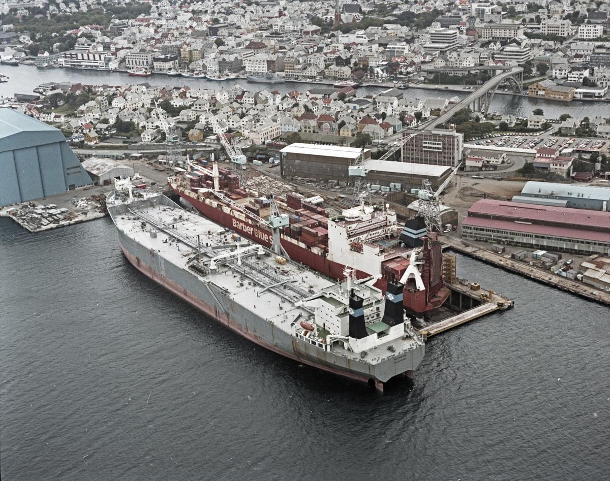 """Flyfoto H.M.V. Oversiktsfoto. Tankskipet """"Polyviking"""" fra Kristiansand ved kai. Frakteskipet Barber Blue Sea i dokk. Haugesund i bakgrunnen."""