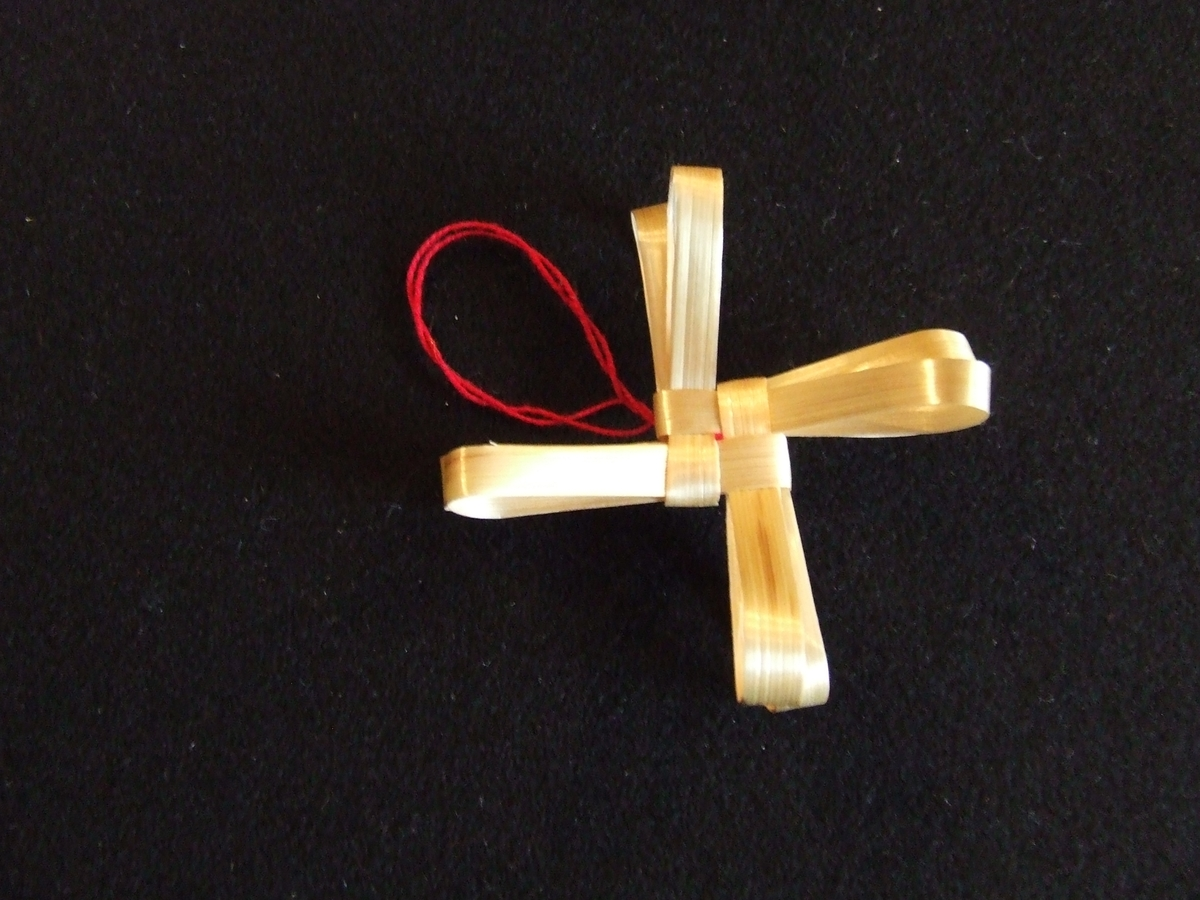 Halmrosett tillverkat av utpressade strån, flätat och böjt. Enkel rosett. Ögla av rött bomullsgarn. 60 mm i diameter.