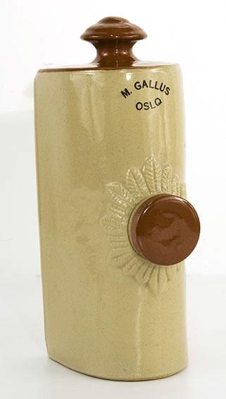 Forsegjort flaske med dekor rund fyllepropp. Avlang med en flat side. Resten er buet. Knott til å bære i på ene side.